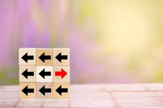 Деревянный блок: красная стрелка, указывающая в противоположную сторону от черных стрелок на деревянном столе.