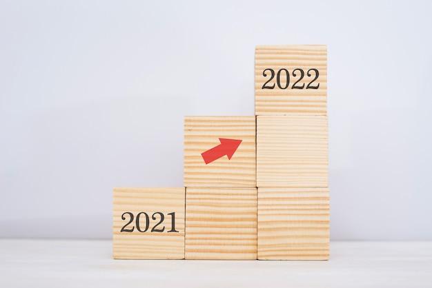 계단으로 쌓는 나무 블록. 화살표가 2021년에서 2022년으로 올라가는 비즈니스 성장 성공 프로세스를 위한 사다리 경력 경로 개념