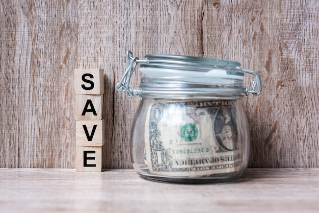 Wood block with save text and american dollar money in glass jar.