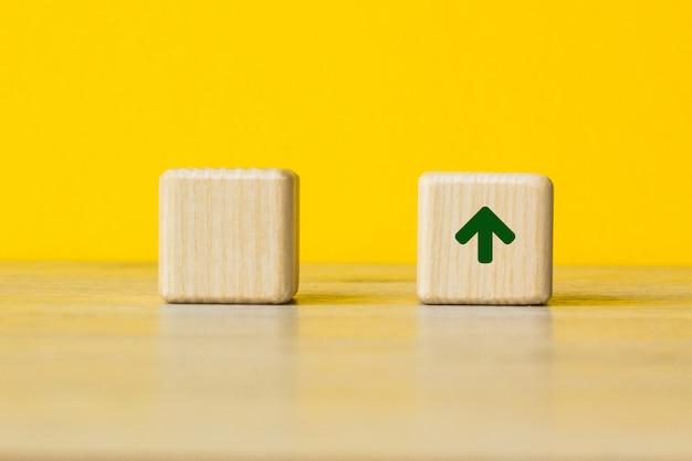 黄色の背景と成長のシンボルと木製のブロック、テキストまたは見出しのコピースペース