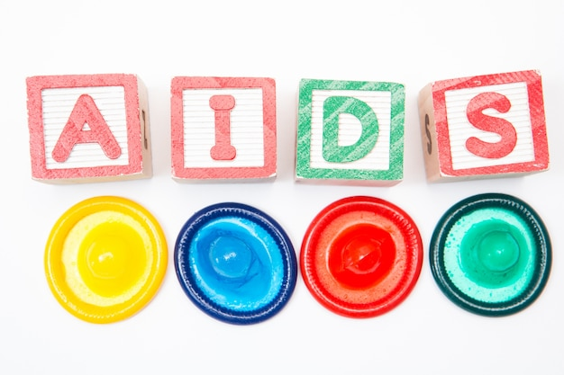 Wood blocks spelling out aids with four colourful condoms