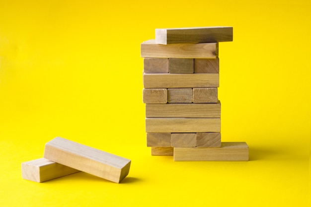 Wood blocks stack game with copy space, yellow background. concept of education, risk,