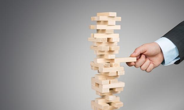 Деревянные блоки укладывают игру с рукой на фоне, концептуальной совместной работы, стратегии и видения.