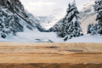 Wood board and mountains with trees in snow
