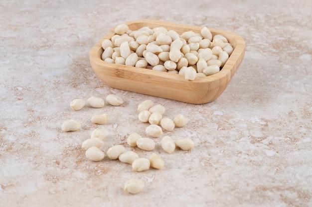 大理石のテーブルに置かれたピーナッツカーネルの木製ボウル。