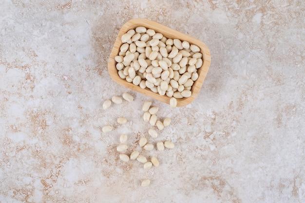 Ciotola di legno di noccioli di arachidi posta su marmo.