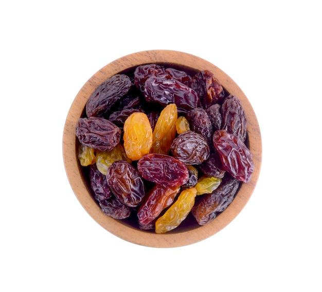 Wood bowl raisins isolated on white.