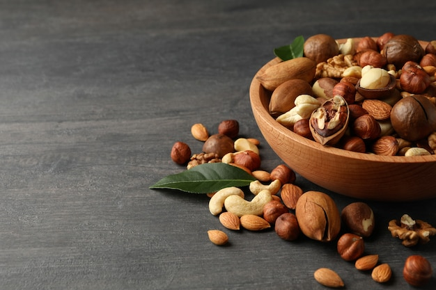 Wood bowl with different tasty nuts on gray wooden