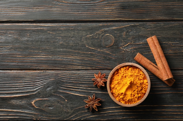 Wood bowl with turmeric and cinnamon on wooden background, top view