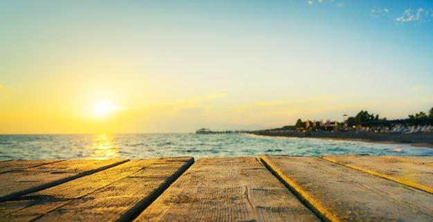 日没時のビーチと海の木製の橋または桟橋。