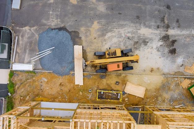 Деревянный каркас здания на новом жилом доме обрамляет вилочный погрузчик с подъемной стрелой в новом доме