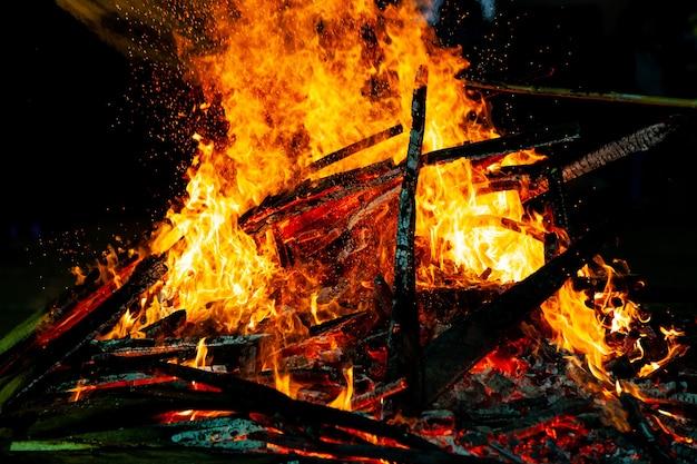 Дрова горящего пламени на черном