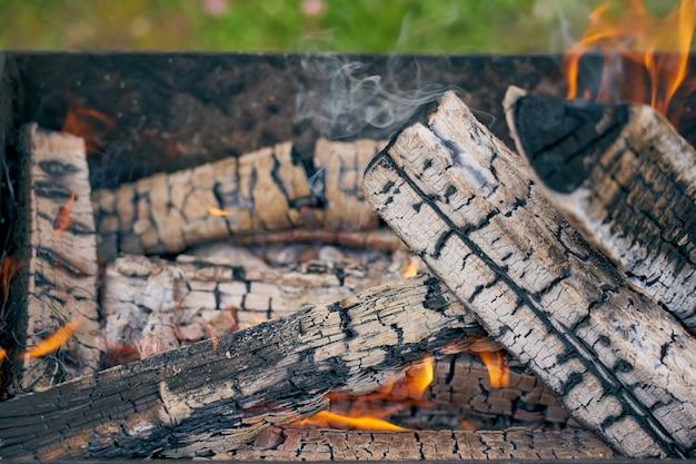 自然の中でグリルで燃えている木材がクローズアップ。