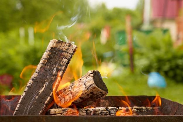 自然の中でグリルで燃える木材。