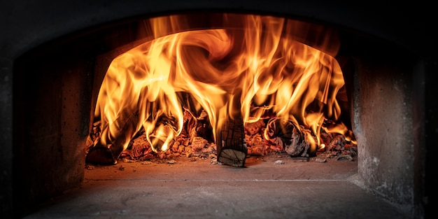 Wood burning inside a wood-burning oven for the preparation of classic italian pizza.