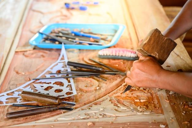 Резчик по дереву используйте деревянный молоток, чтобы перелопатить дерево, долотите ручные инструменты.