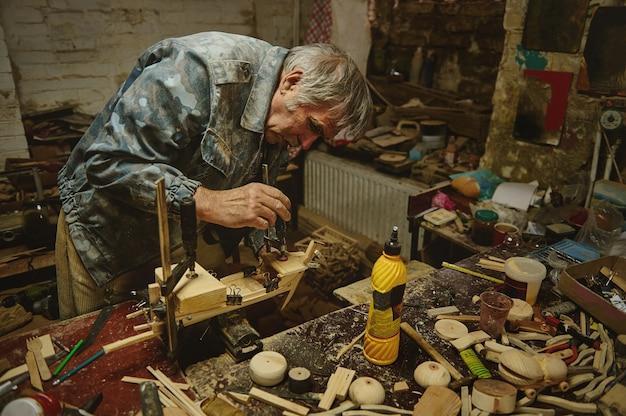 Художник-резчик по дереву работает над созданием модели деревянной игрушки, деревянного парусного корабля ручной работы.