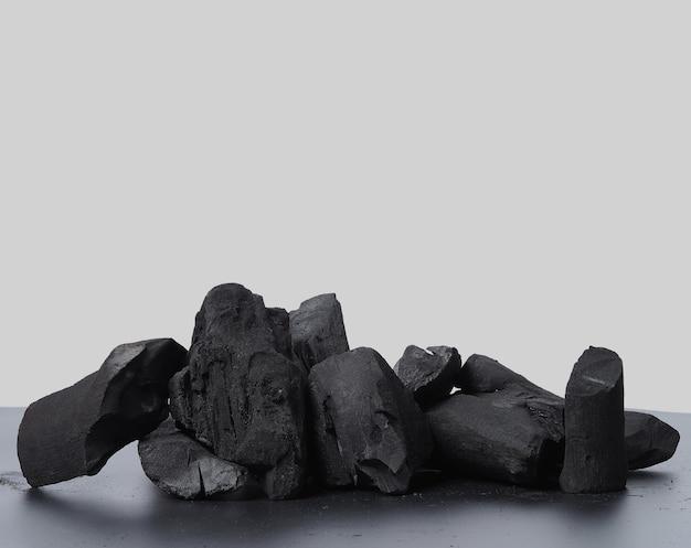 목탄. 검은 질감 바닥에 검은 숯. 그릴 요리 또는 기타 산업에 사용됩니다. 천연 목탄. 목재를 강하게 가열하여 생성되는 블랙 카본 잔류물. 전통 바베큐를 위해