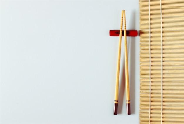 Деревянные палочки для еды на белом столе с бамбуковой циновкой, скопируйте место.