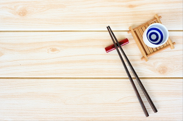 Wood chopsticks on wood table background copy space.