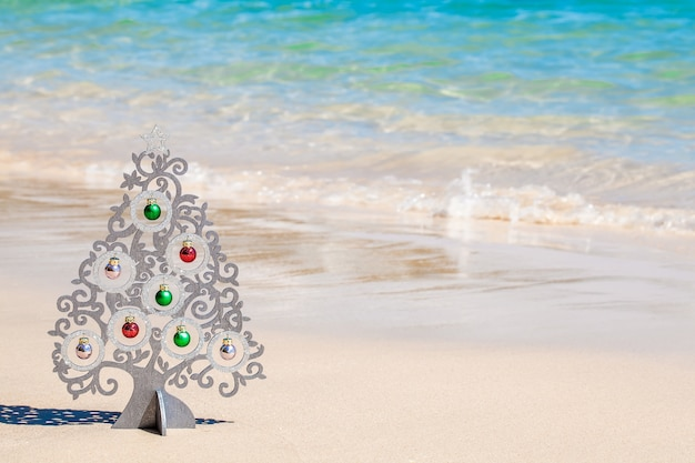 Wood christmas tree with decorations on sea coast with white sand and clear blue water