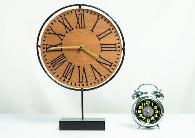 Wood clock with shiny alarm clock isolated on white