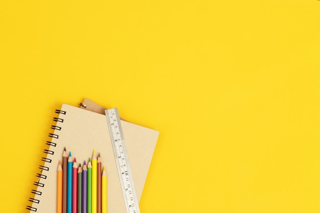 Wood color and ruler placed on a notebook and yellow background.