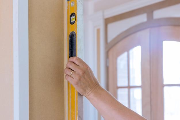 レベリング器具を使用する労働者の建設中の適切なチェックでレベルを使用する木製の柱
