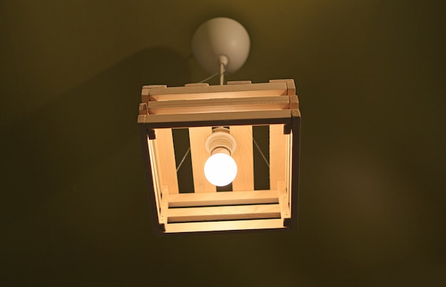 Wood cover lamp hanging on ceiling.