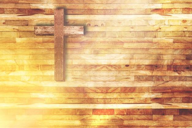 아래에서 빛의 광선으로 교회에서 나무 배경에 나무 십자가