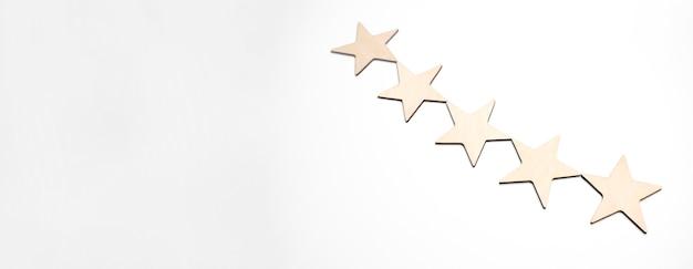 Деревянный куб пятизвездочной формы на белом фоне деревянный стол. блок 5 звезд оценил лучшую концепцию качества обслуживания. награда победителей за высокое качество голосования за высокое качество.