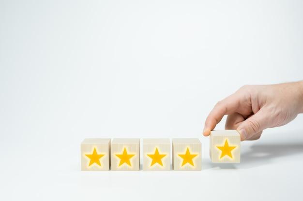 골드 스타 징후와 나무 큐브입니다. 남자 손 나무 5 별 모양을 넣어. best excellent services rating 고객 경험 개념