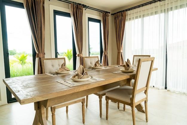 カーテンと窓のある部屋の木製ダイニングテーブル