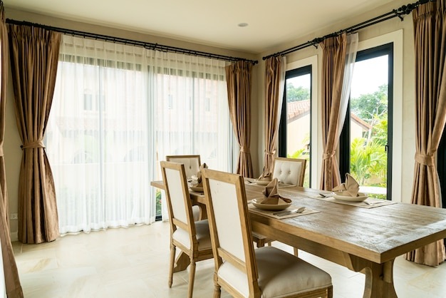 커튼과 창문이있는 방에있는 나무 식탁