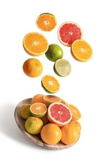 白い背景から分離された、オレンジとみかんの盛り合わせが飛んでいる木製の皿