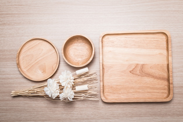 Wood dish with dried flower on the wooden background.