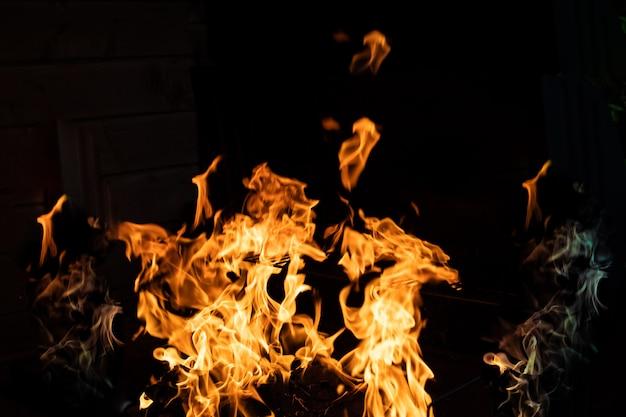 Деревянный огонь на черном фоне. пламя огня на черном фоне. огонь бушует в темноте. костер ночью. пламя танцует. фон оранжевого пламени, темная доска в огне, дым и пепел