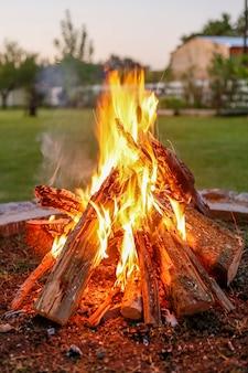 夕暮れ時の庭のベンチと薪の火