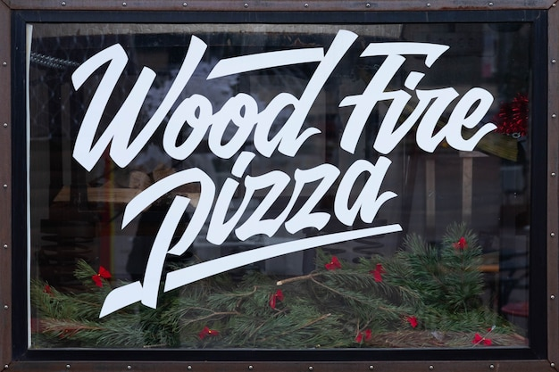 Wood fired pizza, special text written on a glass display case