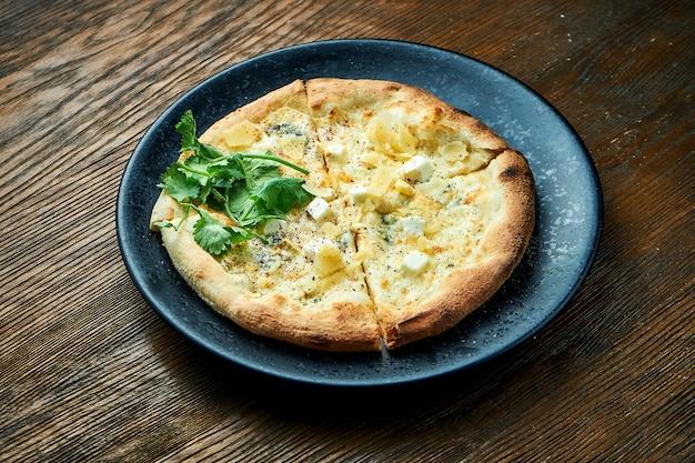 Пицца на дровах с 4 видами сыра и белым соусом с хрустящими боками, подается на черной тарелке на деревянном столе. пицца разновидность итальянской пиццы Premium Фотографии
