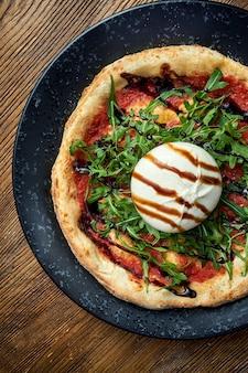 ブッラータ、ルッコラ、レッドソース、バルサミコ酢を使った薪焼きピザ。ピゼットイタリアンピザの一種