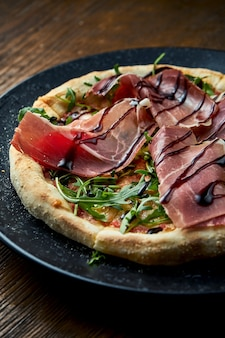 Wood-fired pizza with jamon, arugula, red sauce served on a black plate on a wooden background. pizzette a kind of italian pizza