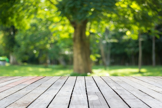 Wood floor with blurred trees of nature park background