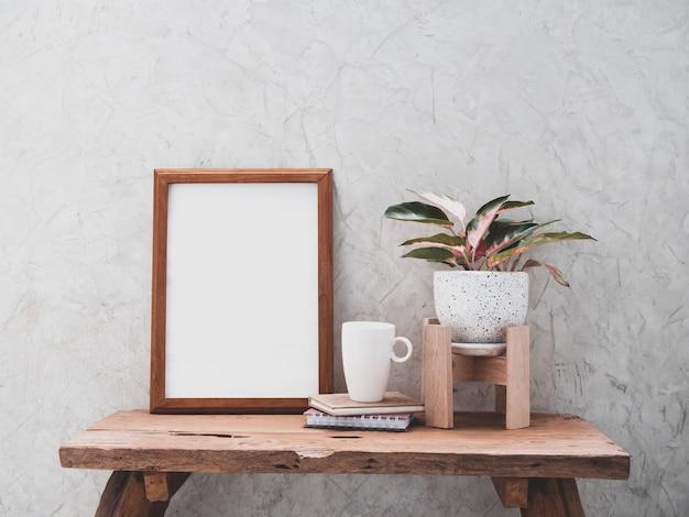 나무 프레임 커피 컵 모의 및 aglaonema houseplant 제품 복사 공간이있는 시멘트 벽면이있는 티크 나무 테이블에 현대적인 흰색과 검은 색 세라믹 용기에 중국 상록수