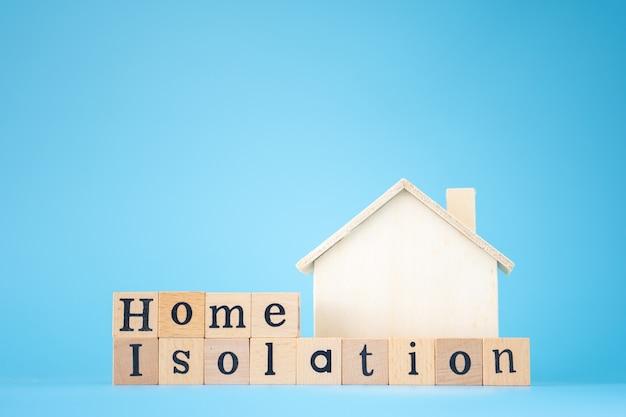 파란색 배경에 'home isolation'이라는 단어가 있는 나무 집과 나무 큐브. 코로나바이러스 전염병 동안 집에 있으십시오.