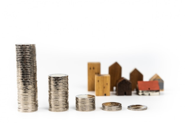 Wood house model and row of coin money on white background