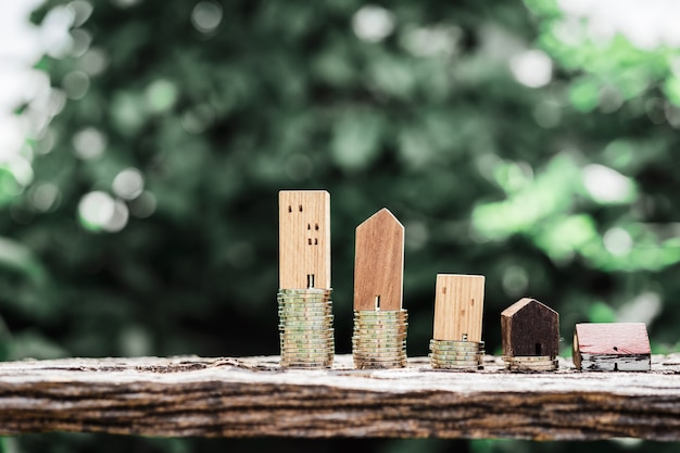 Wood house model and row of coin money on wood table with light nature backgroud.