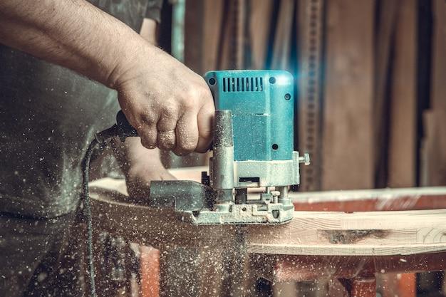 가구 제조업에서 전기 절단기로 목재 밀링. 컬러 토닝. 복사 공간