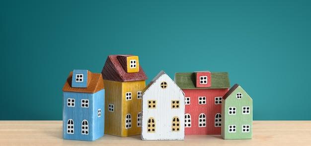 Деревянные миниатюрные красочные дома на деревянном столе и зеленом фоне. ипотека, недвижимость, концепция страхования.