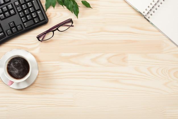 コンピューターのキーボード、一杯のコーヒーと消耗品を備えた木製のオフィスデスクテーブル。コピースペース、フラットレイの上面図。